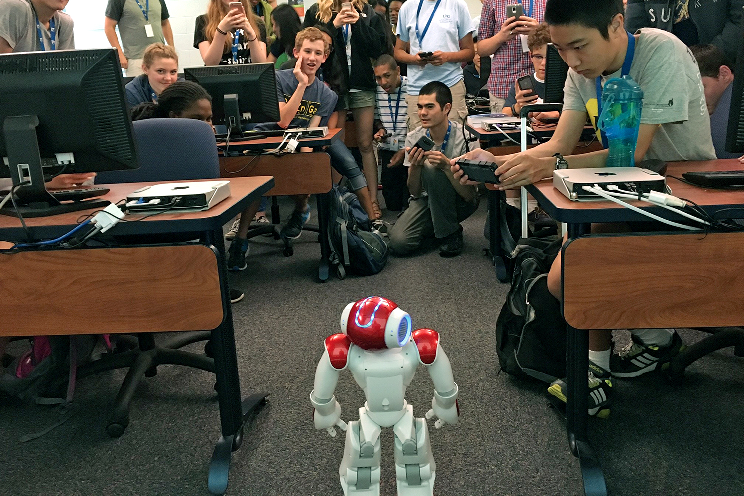 Students watch a small robot