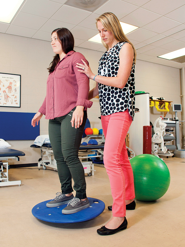 A PT student helping someone with their balance skills.