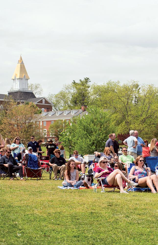 Alumni Weekend - Alumni and family sitting outside.