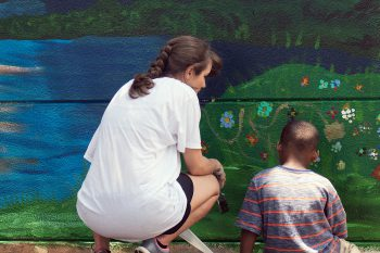 UNG students signed on to work with the Gainesville Housing Authority (GHA) to organize, design, and paint a 9-by-36-foot mural across two white concrete walls at the Melrose Apartments.