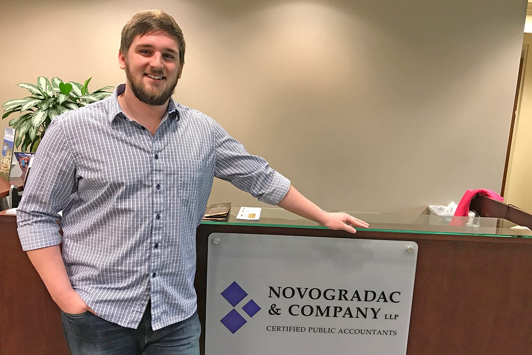 Mike Cottrell College of Business student and senior accounting major Stephan Morgan poses in the lobby of Novagradac and Company, LLP.