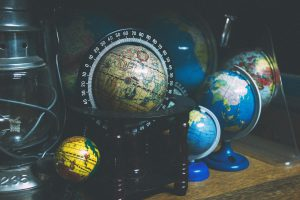 Globes of various sizes sit on a desk.