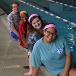 Peer Mentors sitting beside the pool.