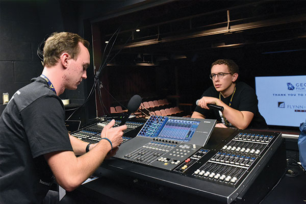Two students with a soundboard