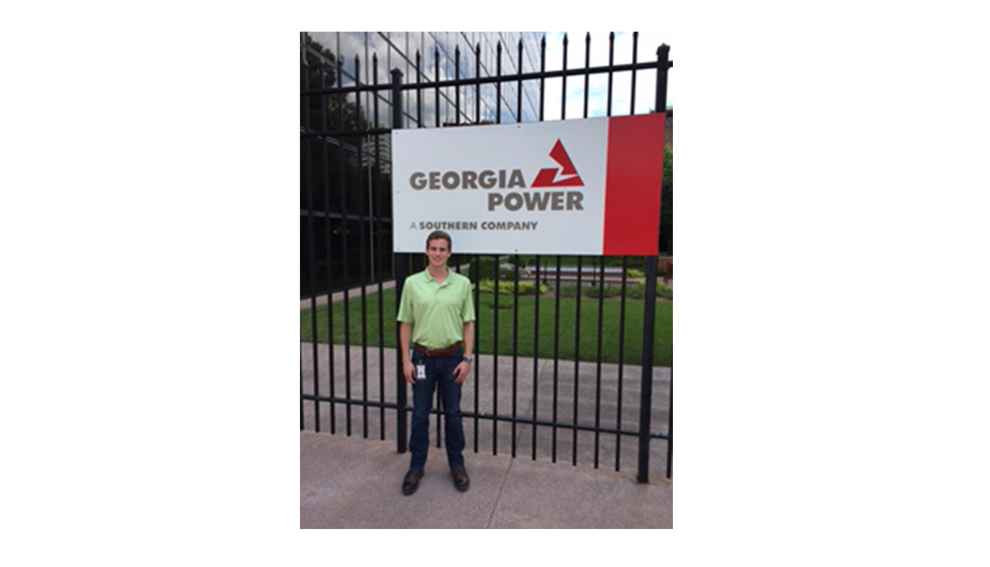 Ethan Webster stands in front of Georgia Power sign