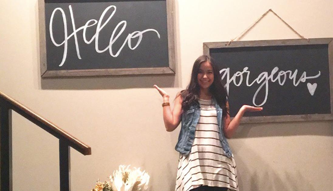 Photo of student with Hello Gorgeous written on chalkboard in background