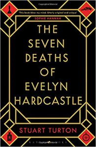The Seven Deaths of Evelyn Hardcastle book cover, black with geometric designs and red diamonds decorating the corners, the diamonds contain black illustrations of a chess piece, a gun, a compass, and a bottle of poison.