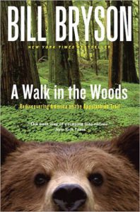 Cover of A Walk in the Woods, showing a scene of the lush green forest floor and the head of a brown bear peaking up from the bottom edge of the cover.