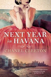 Cover for Next Year in Havana. A Young woman in a pink, 1950s-style gown sits on a blue couch. This image fades into a city scene of Havana and the Cuban coastline underneath.