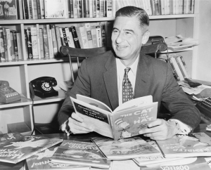 Black and white picture of Dr. Seuss holding a copy of The Cat in the Hat at a desk, with many of his other children's books scattered around him.