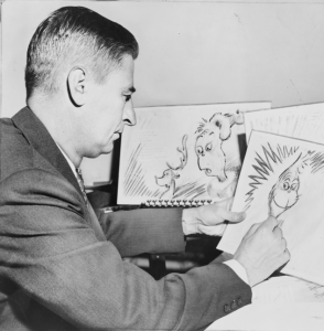 Black and white picture of Dr. Seuss sketching characters for a book or cartoon.