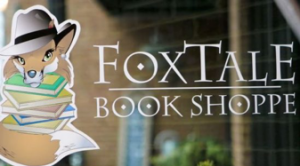 Store window of the FoxTale Book Shoppe featuring their fox and books logo.