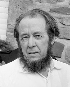 Aleksandr Solzhenitsyn poses for a black and white photograph. He has a short but full beard and a full head of hair.