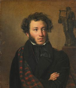 Alexander Pushkin sits for a portrait. He has light skin and brown curly hair. His sideburns come down along his cheeks, but he has no beard or mustache. His arms are folded across his chest.