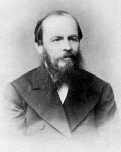 Fyodor Dostoevsky sits for a black and white photograph. He wears a suit. He is balding, but his hair and beard are cleanly kept.