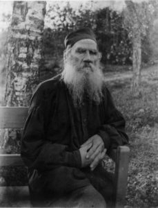 Leo Tolstoy sits for a black and white photograph. His beard is long and split into two. His hands are folded in front of him.