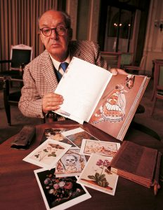 Vladimir Nabokov in 1969 displays one of his books on lepidopterology (a branch of entomology concerning the scientific study of moths and the three superfamilies of butterflies). Colorful illustrations sit on the table in front of him.