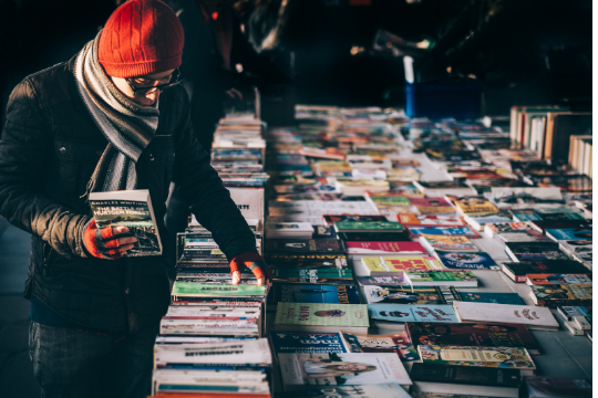 A person in a winter coat, a scarf, and a red hat looks at a selection of paperback books at a street book sale.