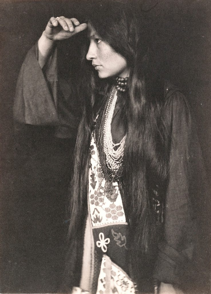 Zitkala-Sa stands with her head to her forehead. She is dressed in a mix of tribal dress and western clothing. The photograph is black and white, taken by Gertrude Kasebier about 1898.