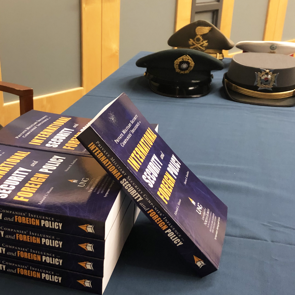 Hats representing foreign militaries sit on a table. In front of them is a stack of blue books. The book is the 2018 ILSS Symposium Monograph, published by the University of North Georgia Press.