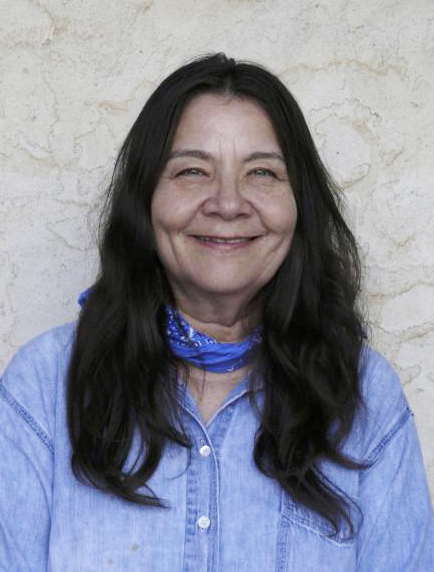Leslie Marmon Silko smiles. She has medium-length black hair and wears a blue shirt and blue handkerchief around her neck.