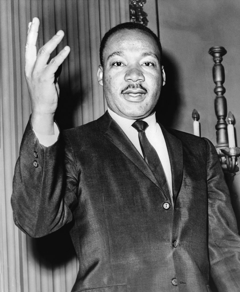 Martin Luther King Jr. stands speaking with his arm raised up.