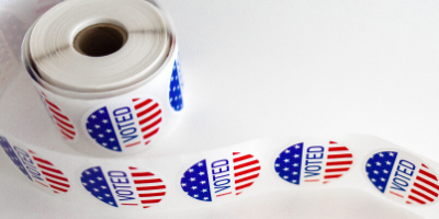 "A roll of stickers that say ""I Voted"" in red, white, and blue."