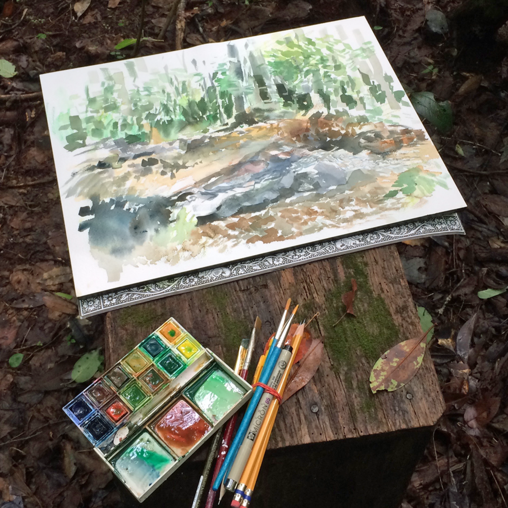 """Painting in the woods."" A watercolor sketchbook, paints, and brushes sits on a wooden stump. The painting is of the surrounding forest and river."