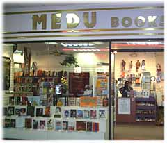 The storefront of Medu Books. The bookstore name is in gold and a line of books sits in the window.