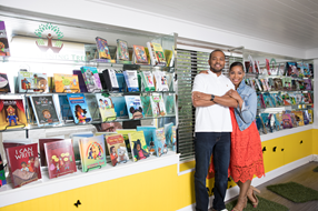 The owners of Listening Tree Books standing inside their store surrounding by books.