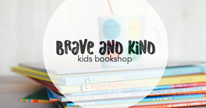 The logo of Brave + Kind Books, a children's bookstore. The name is overlaid on a stack of colorful children's books.