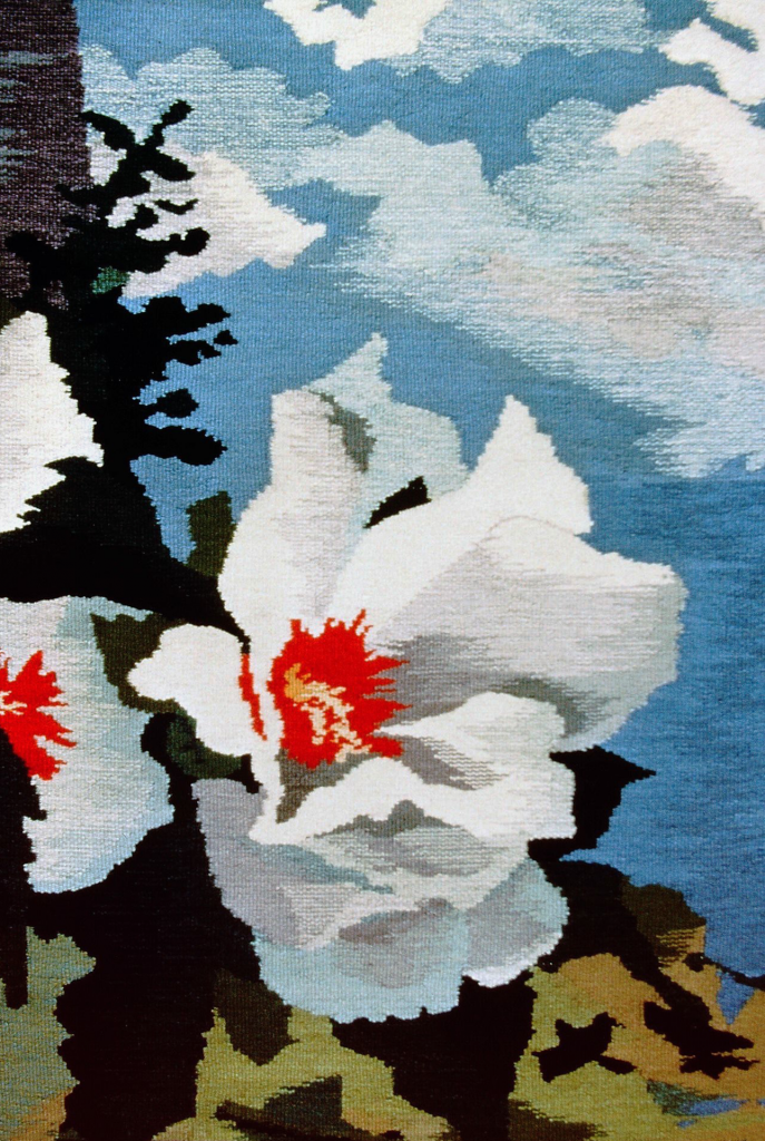"""A tapestry titled """"Althea"""" by Scanlin. It shows a many-petaled white flower with a vibrant red center. A blue sky with white clouds sits beyond the flower."""