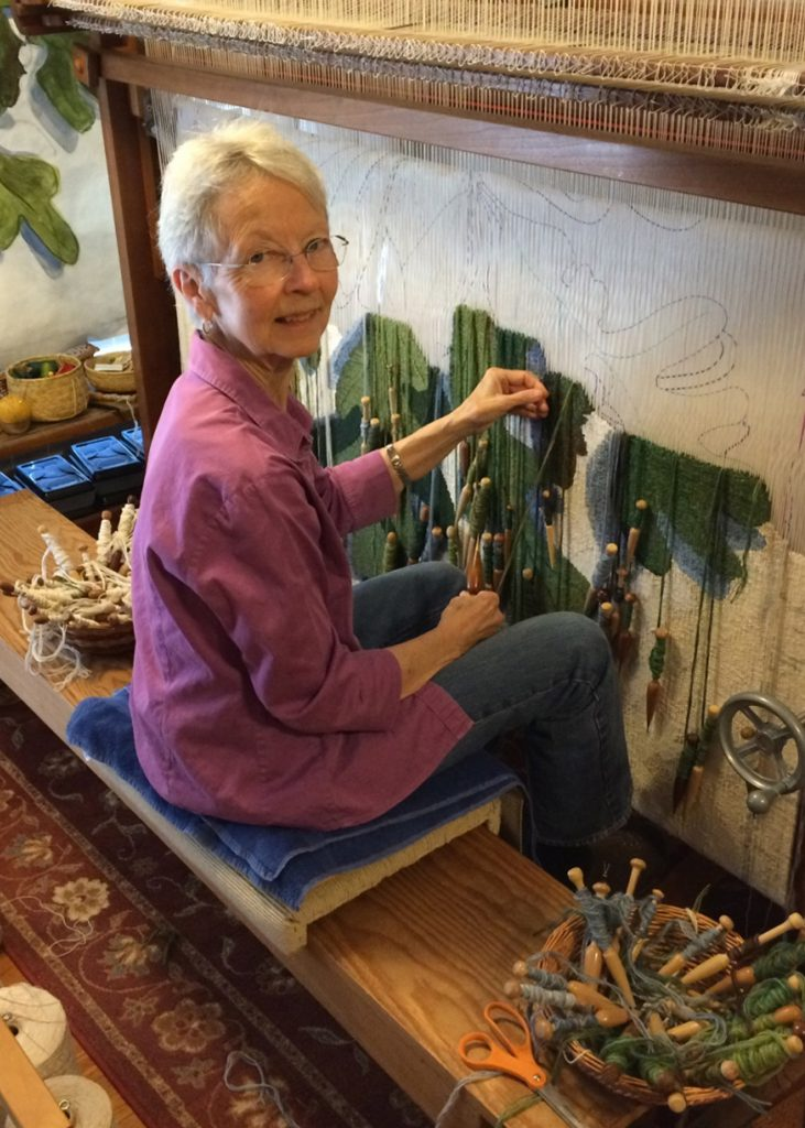 Author Tommye McClure Scanlin sitting at her standing loom.